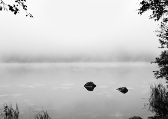 Black and white background. Reflection of stones in tranquil Alps lake at autumn