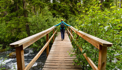 Young traveler woman crossing a bridge on a hiking trail
