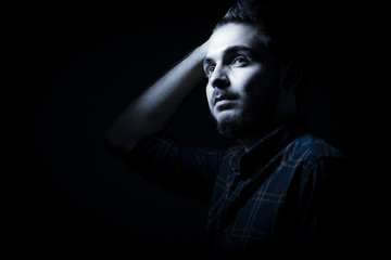 Boy in darkness isolated inside Studio