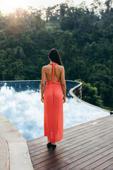 Rear view of woman standing by  swimming pool at luxury resort
