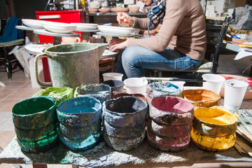 Pottery decorating: work table of a pottery decorator of Caltagirone with different color containers
