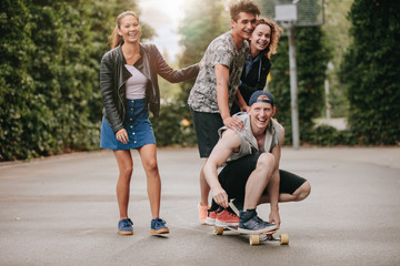 Teenage guys on skateboard with girls