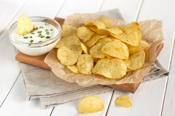 Potato chips on a parchment on a table.