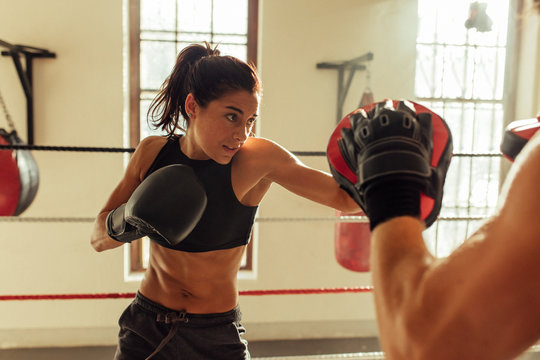 Pretty young woman trains in boxing ring