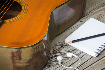 Black pencil with notebook, white headphones and guitar on wooden background
