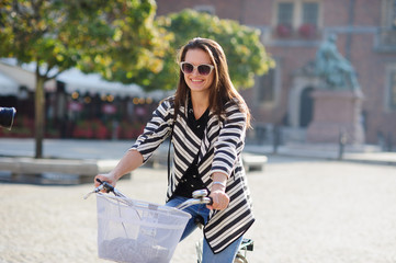 Dark-haired young woman in sunglasses rides by bicycle on a paved pavement.