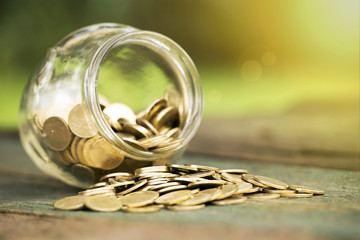 Golden money coins in a glass jar - charity, donation concept