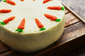 Homemade carrot cake decorated with orange carrots on wooden background