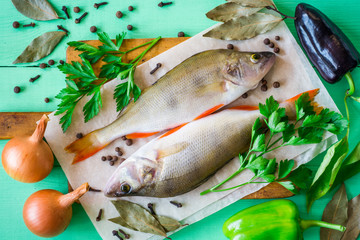 Two raw perch on rustic cutting board with fresh herbs, vegetables and spices on green wooden table