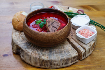 Borsch - traditional russian soup with red beets on the wooden background