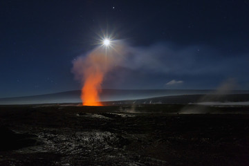 Full moon over Halemaumau Crater within the much larger summit caldera of Kilauea in Hawaii Volcanoes National Park, steaming vents in foreground, Mauna Loa mountain in background; Island of Hawaii, Hawaii, United States of America