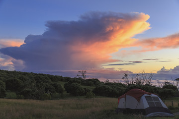 Camp site at Keanakolu State Park with cumulonimbus sunrise clouds; Island of Hawaii, Hawaii, United States of America