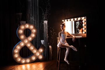Young teenage ballerina is dancing and posing in the photostudio with black walls