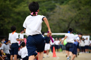 Students running in a field. Sports day in Japan.
