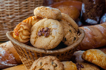 Freshly baked cookies and sweet pastries in the basket on wooden table