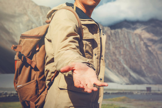 Young travel man lending a helping hand in outdoor mountain scenery.