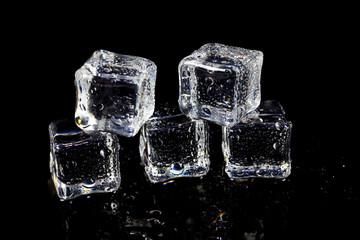 Fototapeta ice cubes reflection on black table background.