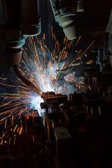 Team robot welding automotive part in factory