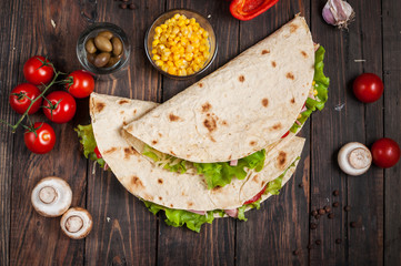 Sandwiches twisted roll Tortilla two pieces and vegetables on a wooden background