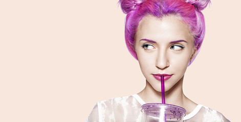 Young woman with multi-colored hair in a white dress drinks from a beautiful colored glass with a straw