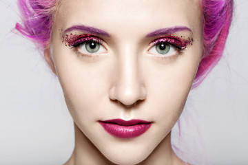 Close-up of a woman's face with a shiny trendy makeup in violet tones with sparkles