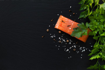 Preparing fresh seafood in the kitchen with gourmet salmon fillet surrounded by fresh herbs and spices on black stone background