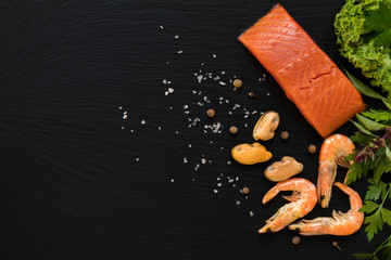 Preparing fresh seafood in the kitchen with gourmet salmon fillet, pink shrimp and mussels surrounded by fresh herbs and spices on black stone background