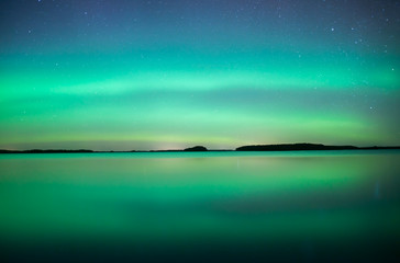 Wall Mural - Northern lights dancing over calm lake in Sweden