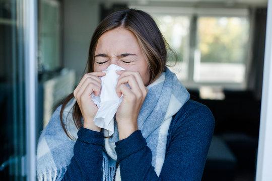 Frau nießt in ein Taschentuch
