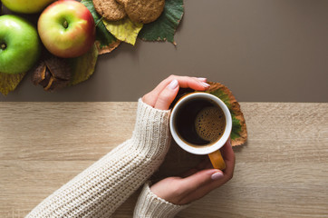 Hands holding cup of coffee with apples and cookies on wooden table indoors autumn time