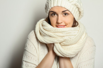 Beautiful natural young smiling brunette woman wearing knitted sweater,  scarf and hat.  Winter fashion concept.