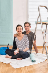 couple wallpapering their new flat take a break with a coffee