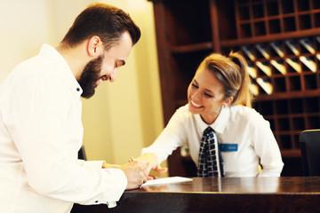 Man signing bill in hotel