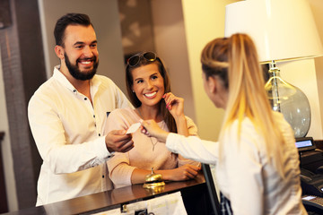 Couple at reception desk in hotel