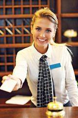 Pretty receptionist giving key card