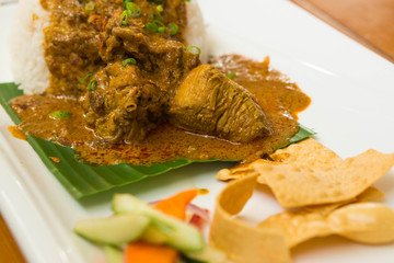 Malaysian food,  delicious Chicken curry with salad on rice in white plate