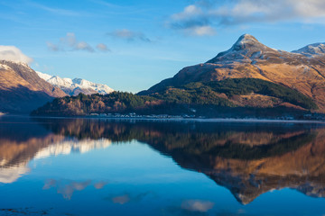 Mountains with mirror like reflections upon Loch in Scotland, UK