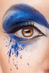 Close up image of an eye with blue fantasy make up