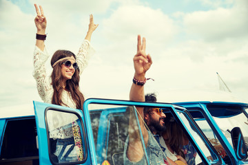 hippie friends over minivan car showing peace sign