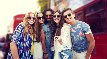 smiling hippie friends with selfie stick in london