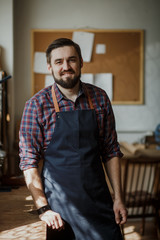 Portrait Male Master apron in his workshop. Small business