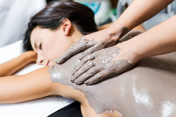 Beautiful young woman having clay body mask apply by beautician.