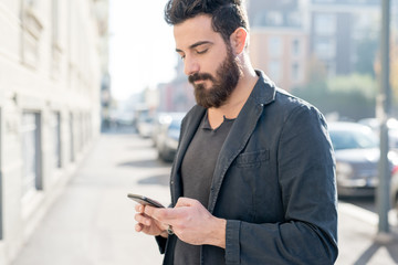 young man bearded outdoor using smartphone