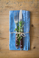 Fork, knife and napkin decorated with rosemary and thyme on rustic wooden background