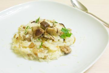 Risotto with mushrooms, parmesan cheese and parsley on a wooden background