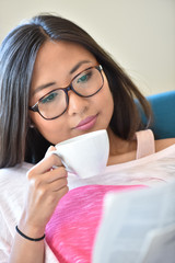 Asian girl relaxing with coffee and newspaper