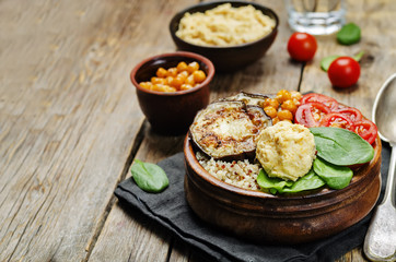 Mediterranean quinoa hummus bowl with eggplants, tomatoes and sp