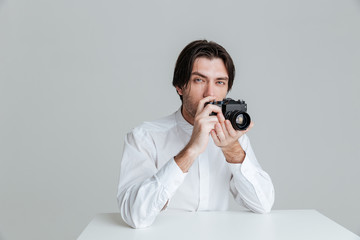 Man ready to make photo while sitting at the table