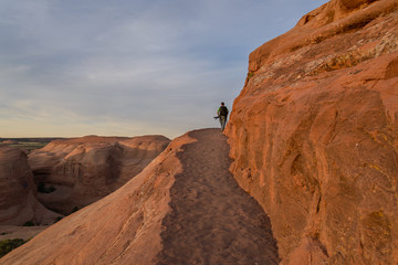 Photographer in action in the desert, Moab  / Photographer in the desert of Moab prepares for shooting, Moab. UTAH