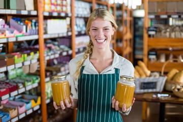 Smiling female staff holding jars of honey in supermarket